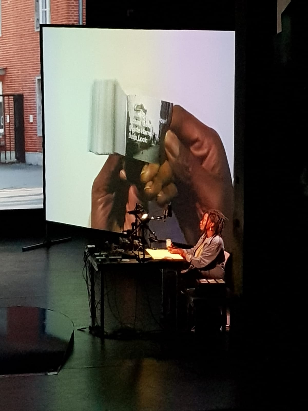 Woman with Brown skin sits at a table.. The screen behind her projects the image of her hands holding a flip book.