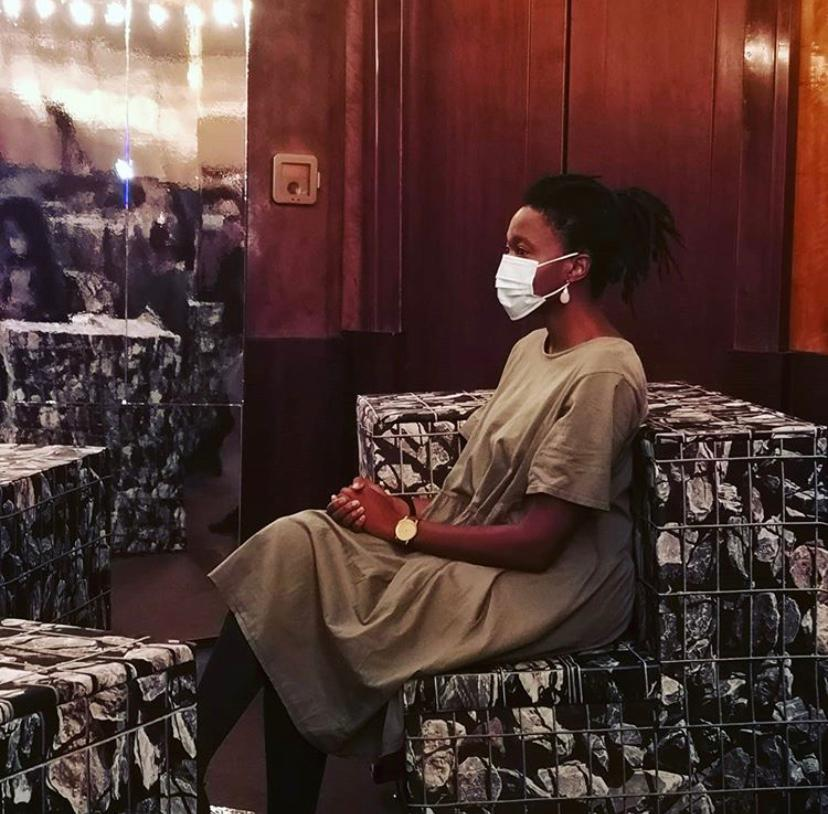 A woman withbrown skin sits wearing a mask.