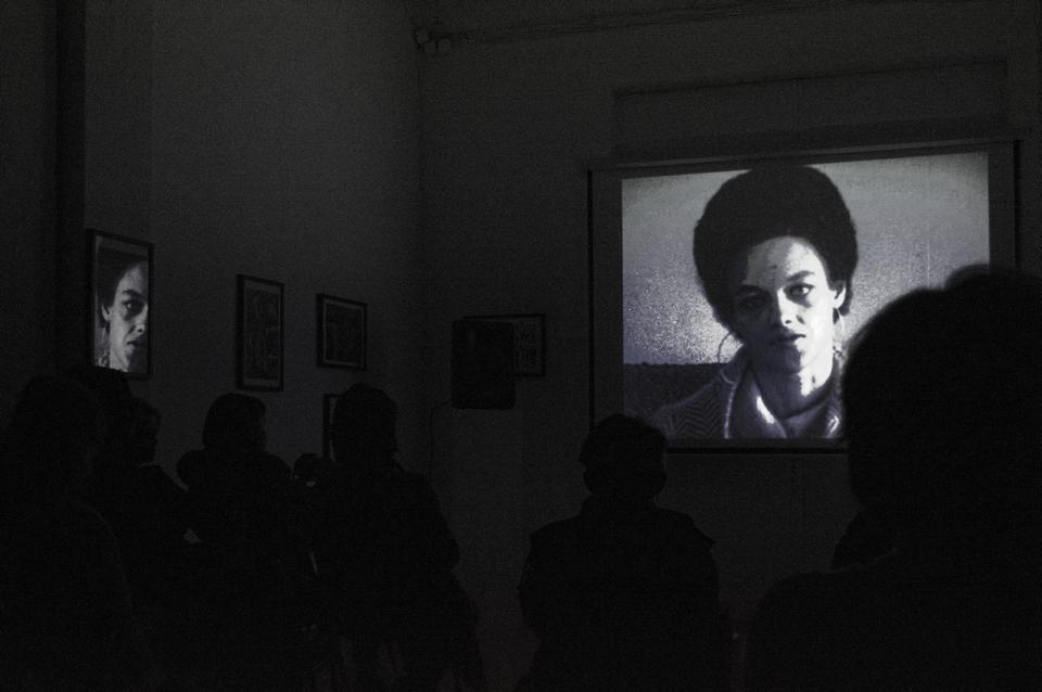 Image of Kathleen Cleaver projected ona wall, audience in dark in forground.
